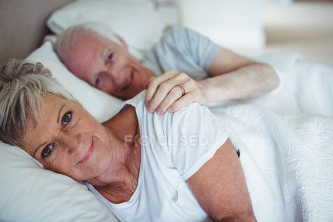 Couple âgé souriant couché sur le lit dans la chambre — Photo de stock
