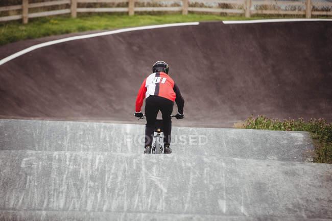 Вид сзади велосипедиста на велосипеде BMX в скейтпарке — стоковое фото