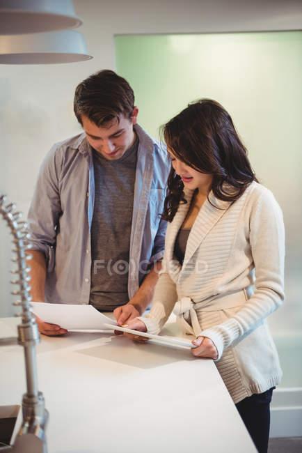 Couple discuter sur tablette numérique dans la cuisine à la maison — Photo de stock