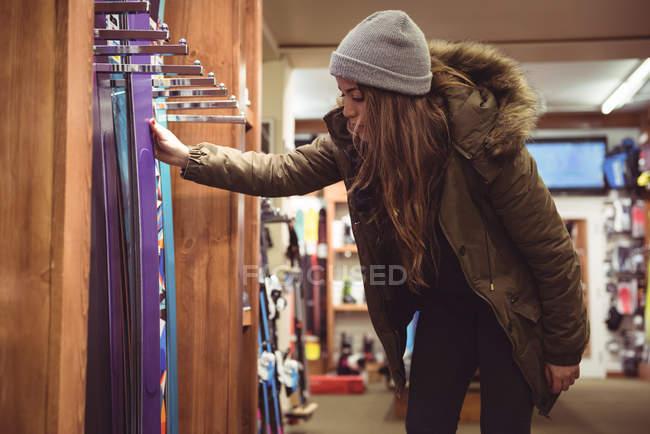 Bella donna selezione sci in un negozio — Foto stock