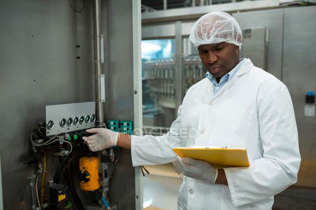 Уверенный работник мужского пола держит планшет во время работы машины на соковом заводе — стоковое фото