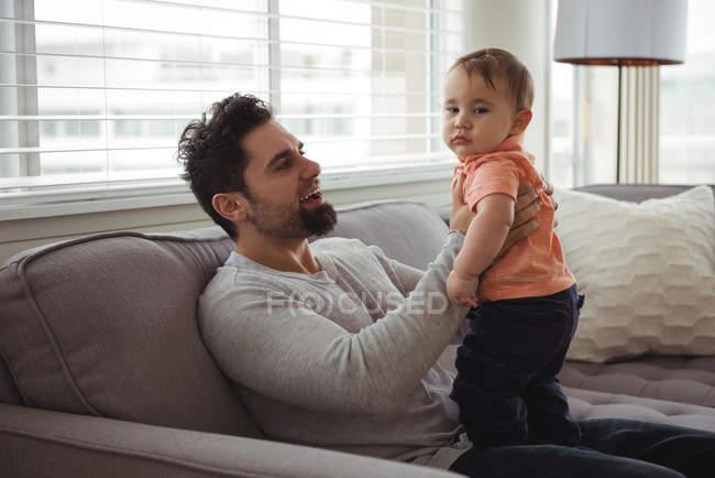 Père jouant avec son bébé sur le canapé dans le salon à la maison — Photo de stock