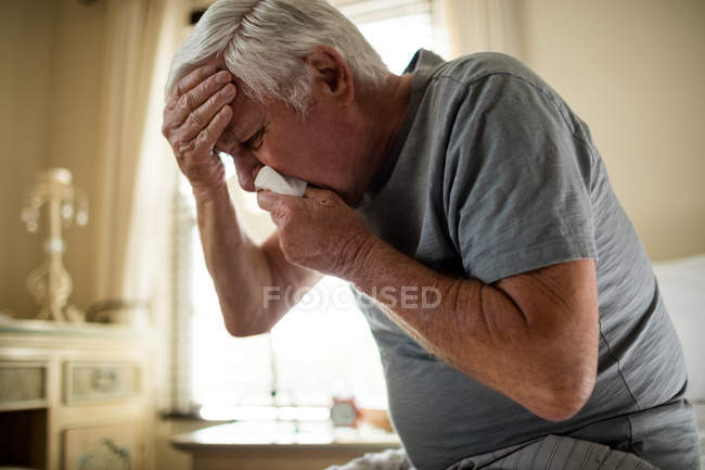 Senior man using a tissue to blowing nose in the bedroom at home — Stock Photo