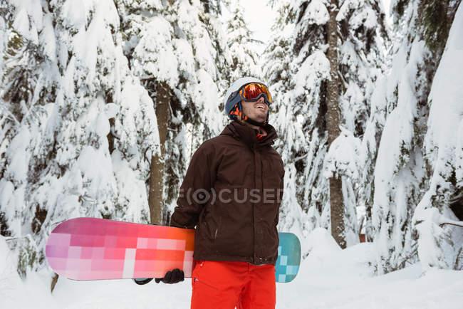 Homem de pé e segurando uma prancha de snowboard na montanha coberta de neve — Fotografia de Stock
