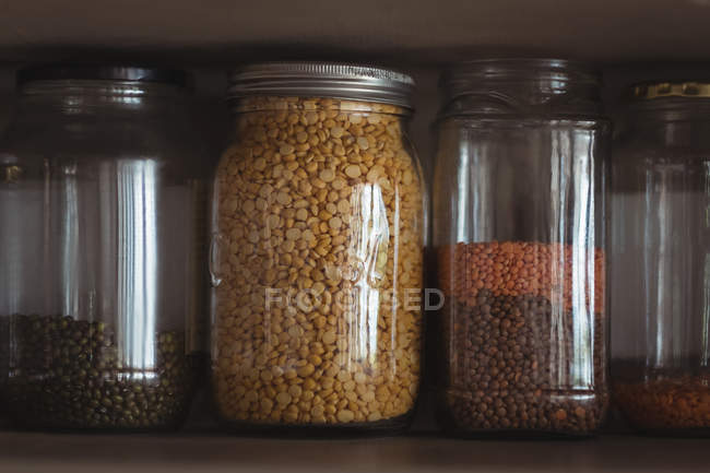 Закри різних сочевиця і квасолі в банки в кухонній полиці — стокове фото