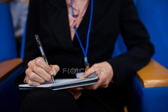 Mid section of female business executive participating in a business meeting at conference center — Stock Photo