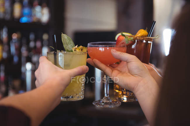 Close-up of friends toasting with beer and cocktail glasses in bar — Stock Photo