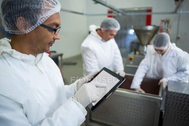 Різник using цифровий планшетний при колег, що працюють у фоновому режимі на заводі м'яса — стокове фото