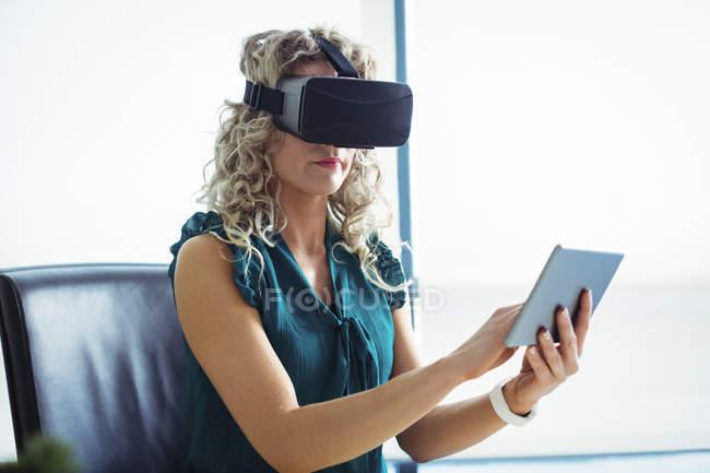Business executive con auricolare realtà virtuale e tablet digitale in ufficio — Foto stock