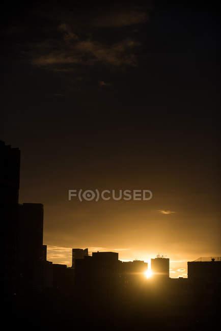Vue tranquille des silhouettes du paysage urbain au coucher du soleil — Photo de stock