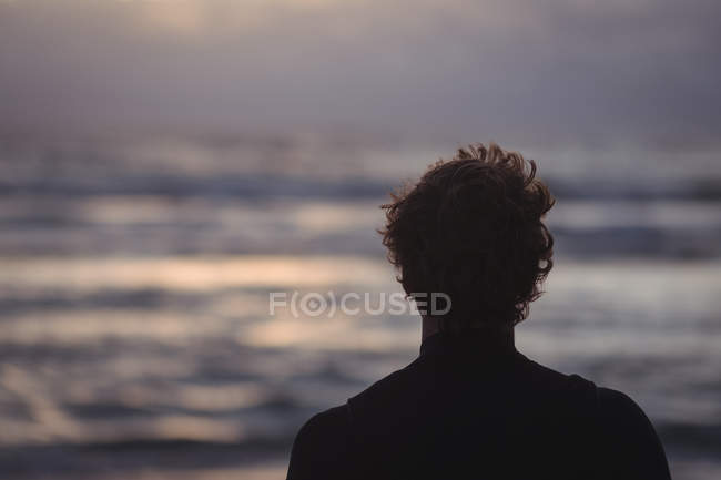 Silhouette of a surfer by sea at dusk — Stockfoto