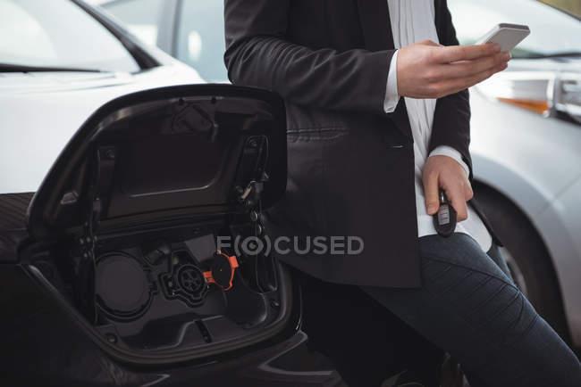 Partie médiane de la femme debout à côté de la voiture électrique et en utilisant le téléphone mobile — Photo de stock