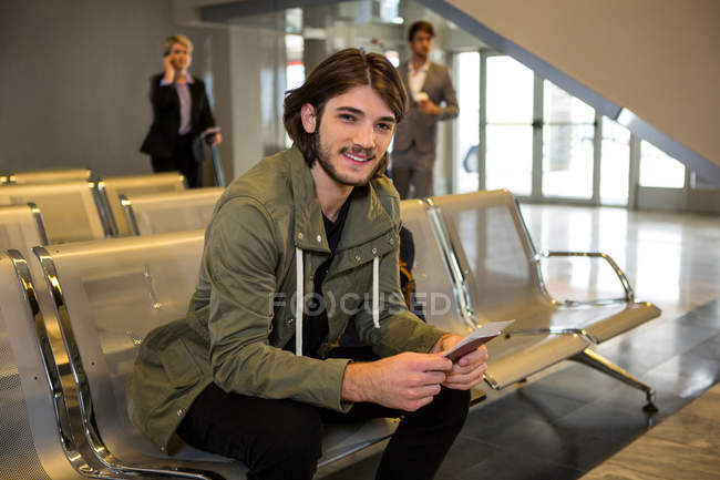 Man with passport and boarding pass sitting in waiting area at airport terminal — Stock Photo