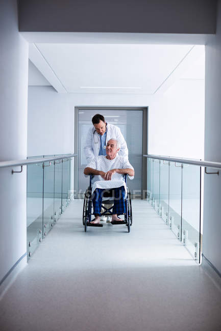 Doctor interacting with male senior patient on a wheelchair in the passageway — Stock Photo