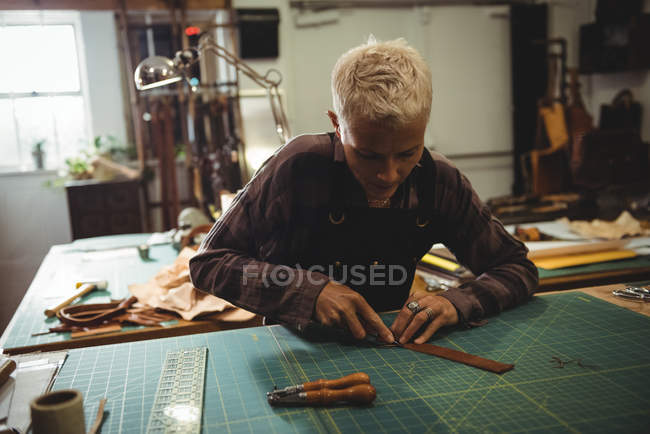 Attentive craftswoman cutting a piece of leather in workshop — Stock Photo