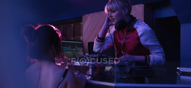 Female dj playing music while interacting with woman at bar — Stock Photo