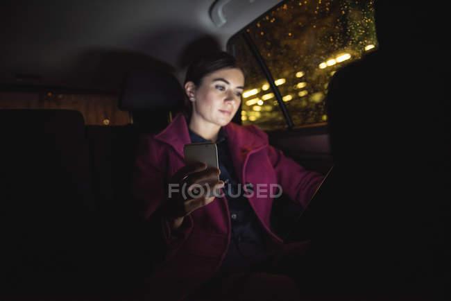 Bella donna d'affari utilizzando tablet digitale e telefono in auto — Foto stock