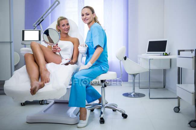Женщина-дерматолог и пациент улыбается на камеру в клинике — стоковое фото