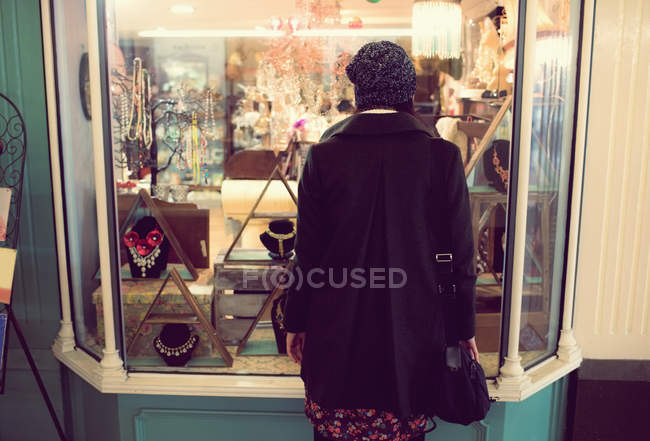 Rear view of woman looking at jewelry counter in supermarket — Stock Photo