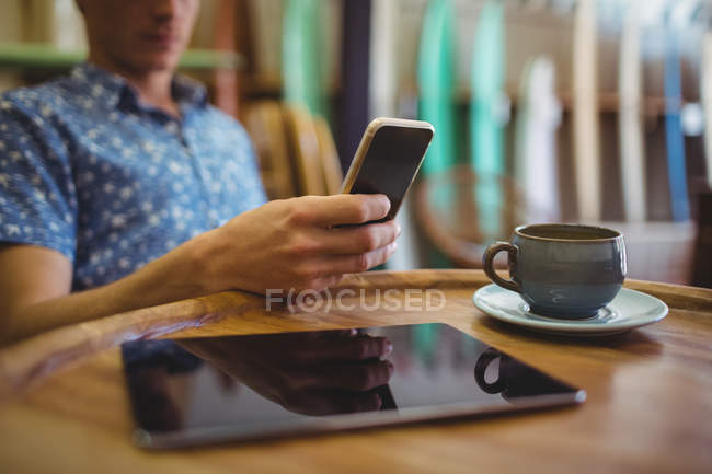 Close-up of man sitting in surfboard shop using mobile phone — Stock Photo