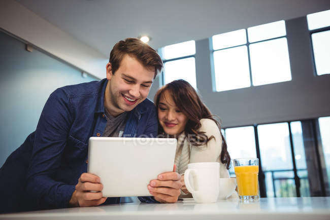 Paar nutzt digitales Tablet beim Frühstück zu Hause — Stockfoto