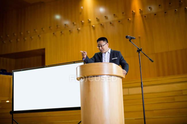 Uomo business executive tenendo un discorso al centro congressi — Foto stock