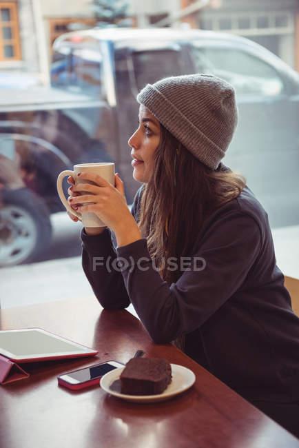 Mujer con ropa de invierno tomando café en el restaurante - foto de stock