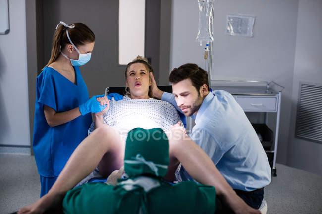 Medico esaminando donna incinta durante il parto in sala operatoria — Foto stock