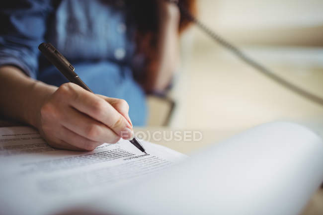 Hand of pregnant businesswoman writing on paper documents in office — Stock Photo