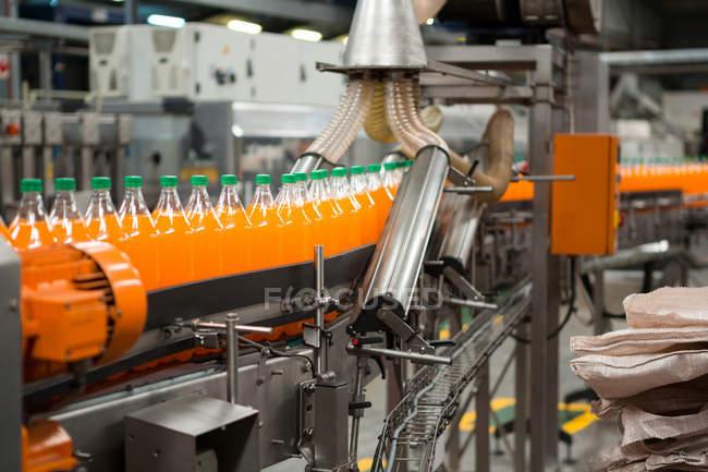Процес упаковки пляшок помаранчевий прохолодними напоями в заводу — стокове фото
