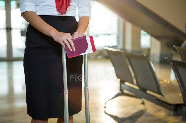 Meados de uma hospedeira aérea com cartão de embarque e saco de carrinho no terminal do aeroporto — Fotografia de Stock