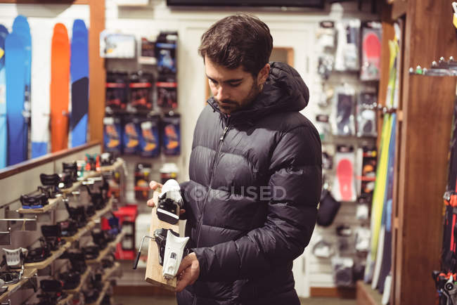 Handsome man selecting ski binding in a shop — Stock Photo