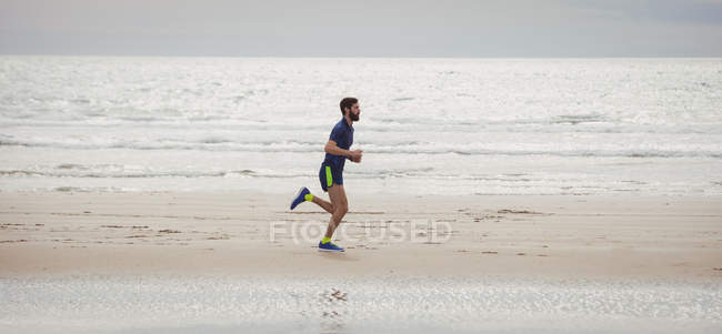 Handsome athlete running along beach — Stock Photo
