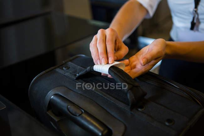 Personal femenino colocar etiqueta de registro para el equipaje en la terminal del aeropuerto - foto de stock
