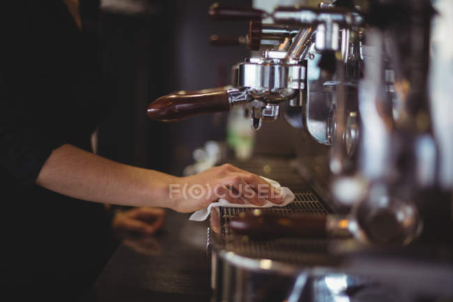 Mid section of waitress wiping espresso machine with napkin in cafe — Stock Photo