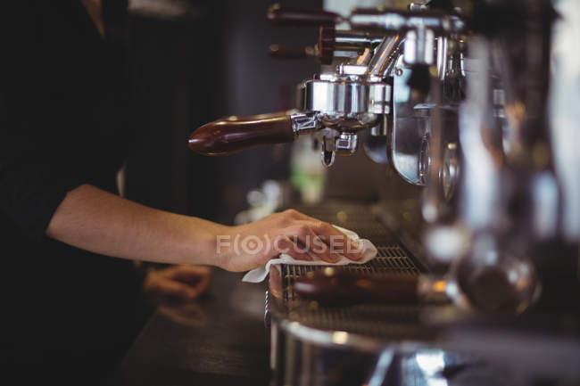 Mittleren Bereich der Kellnerin, die Espresso-Maschine mit Serviette abwischen, im café — Stockfoto