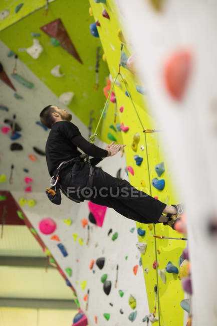 Man practicing rock climbing on artificial climbing wall in gym — Stock Photo