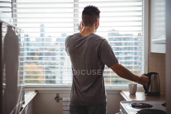 Задний вид человека разговаривающего по мобильному телефону на кухне дома — стоковое фото