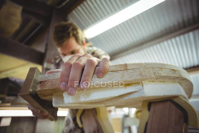 Крупный план человека, делающего доску для серфинга в мастерской — стоковое фото