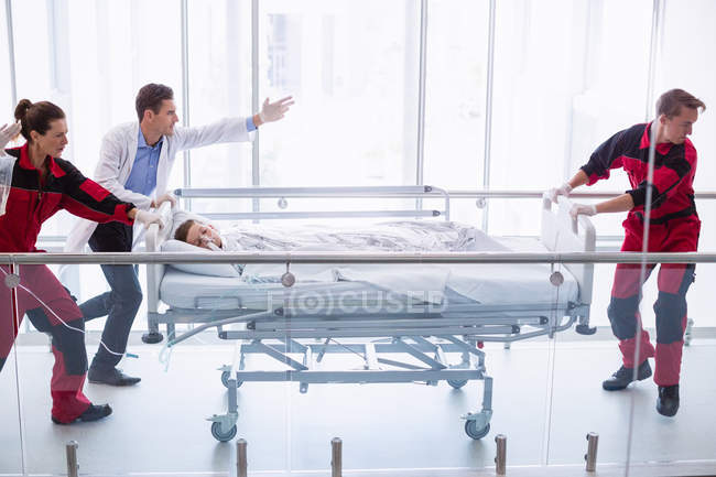 Doctors pushing emergency stretcher bed in corridor at hospital — Stock Photo