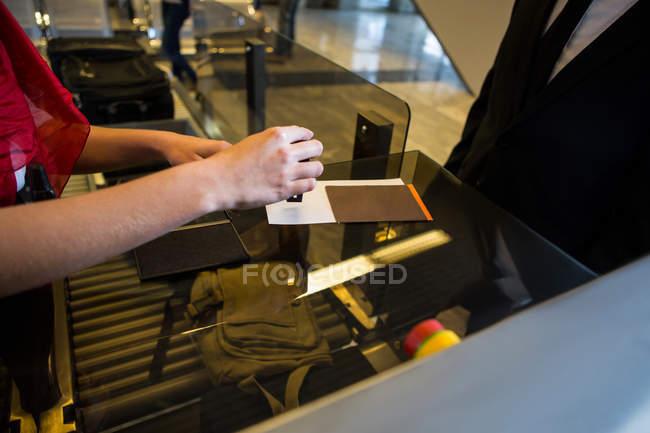 Meados de seção de pessoal feminino colocar um selo no cartão de embarque — Fotografia de Stock