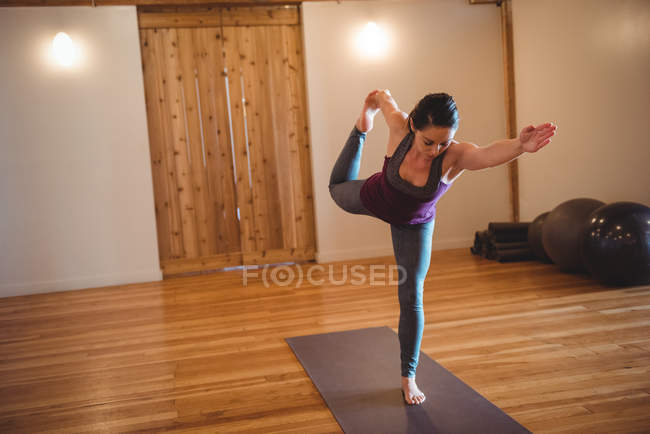 Woman balancing while practicing yoga in fitness studio — Stock Photo