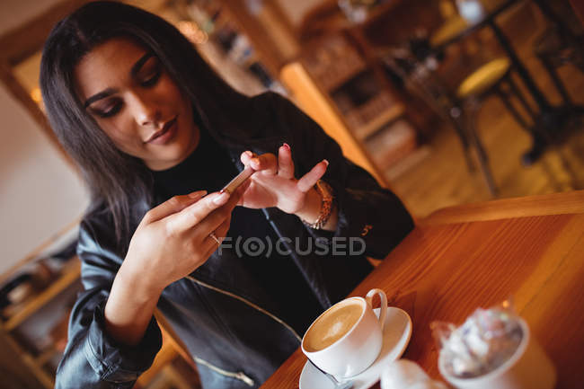 Beautiful woman clicking photo of coffee from mobile phone in cafe — Stock Photo