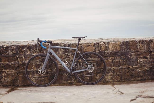Bicicleta estacionada contra a parede costeira frágil — Fotografia de Stock