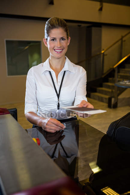 Female staff holding boarding pass at counter in airport terminal — Stock Photo