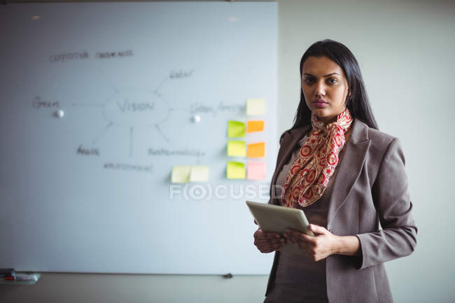 Portrait of businesswoman holding digital tablet in office — Stock Photo