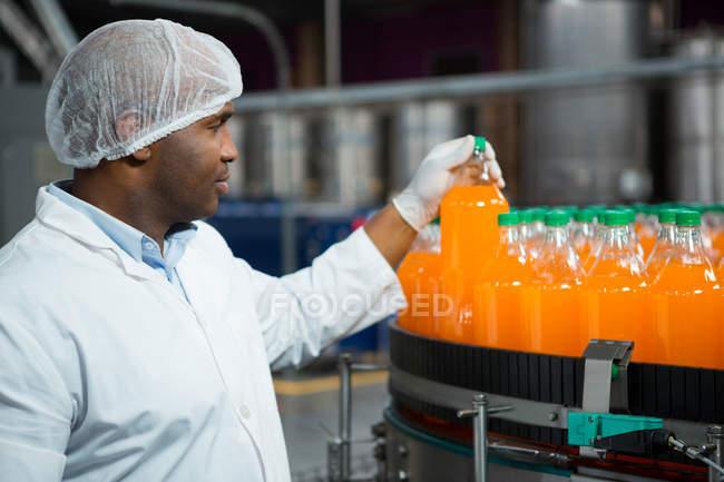 Чоловічий працівник перевірка апельсиновий сік пляшки заводі — стокове фото