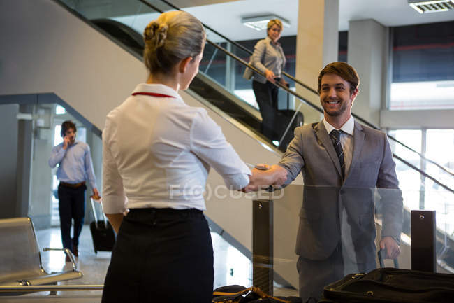 Female staff checking boarding pass of passengers at check-in counter in airport — Stock Photo