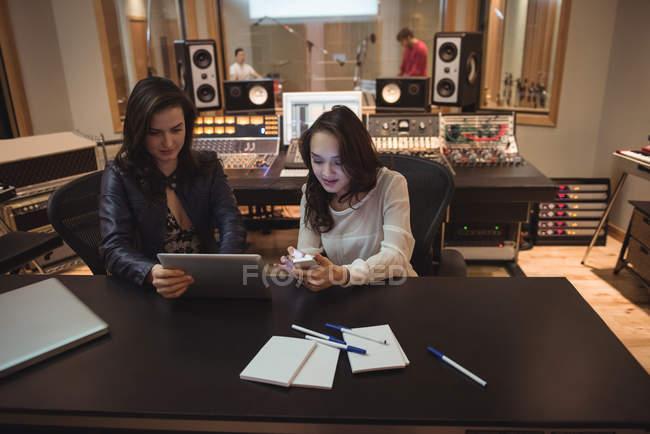 Tontechniker mit digitalem Tablet und Handy im Tonstudio — Stockfoto