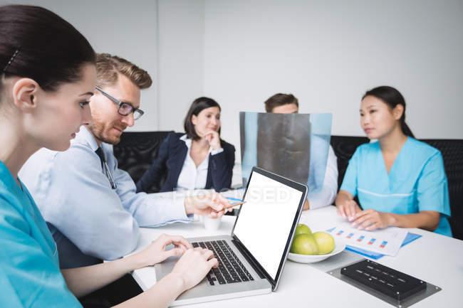 Doctores discutiendo sobre laptop en reunión en sala de conferencias - foto de stock